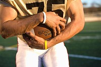 American football player, in gold football strip, clutching ball in hands on pitch, close-up, front view, mid-section