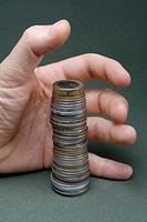 Man holding hand around stack of coins, close up of hand, studio shot