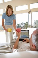 Senior man relaxing on sofa at home, listening to music on headphones, using laptop, mature woman serving refreshments, smiling, rear view