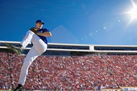 Baseball pitcher, in blue uniform, preparing to throw ball during competitive game, side view lens flare, surface level