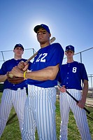 Three baseball players, in blue uniforms and caps, standing on pitch, portrait, low angle view backlit