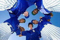 Baseball team, in blue uniform, standing in huddle, smiling, portrait, upward view