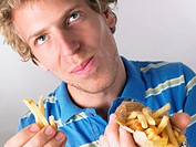 Young man eating fries, close-up