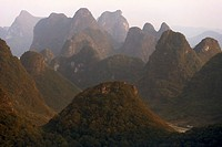 China, Guangxi Province, Guilin, Yangshuo, limestone peaks at sunset