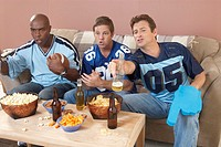 Three men watching football in living room