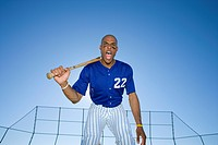 Baseball batter, wearing number ÔÇÿ22ÔÇÖ blue uniform, standing on pitch with bat resting on shoulder, shouting, front view, portrait, low angle view ...