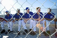 Baseball team sitting on bench in stand during competitive baseball game, view through wire fence, front view lens flare