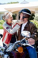Senior man sitting on motorbike on driveway, senior woman adjusting strap of manÔÇÖs crash helmet, smiling, side view