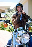 Senior man sitting on motorbike on driveway, adjusting crash helmet strap, smiling, front view, portrait