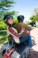 Senior couple riding on motorbike, senior woman looking over shoulder, smiling, rear view, portrait