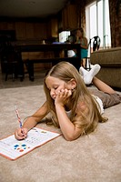 young girl does her homework on floor, older sister in background