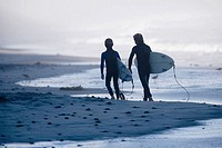 Two young boys walking down and sand and pebblestone beach carrying there