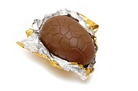 Milk chocolate easter egg in gold foil on white background