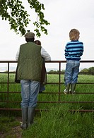 Father with two children 5-6 standing by fence in countryside (thumbnail)