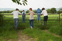 Parents with three children 5_9 standing on fence in countryside