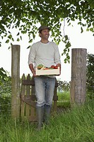 Man carrying crate of fruit and vegetables in countryside