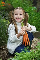 Girl 5-6 holding carrots in garden (thumbnail)