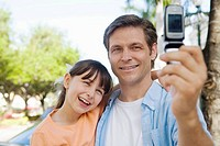 caucasians; dad, age 30 to 40, daughter, age 9, camera phone, smiling, bonding