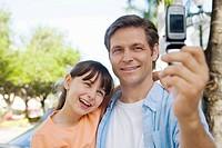caucasians; dad, age 30 to 40, daughter, age 9, camera phone, smiling, bonding