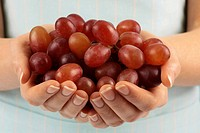 Woman With Handful Of Red Grapes
