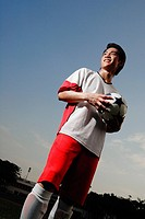 Soccer player holding soccer ball, looking away
