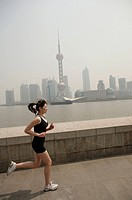 Young woman jogging in city, Oriental Pearl TV tower in background