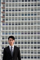 Businessman looking at camera, building behind him