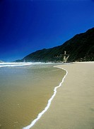 Looking along deserted beach on the Garden Route near the town of Wilderness, South Africa