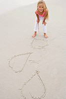 Girl drawing hearts on the sand