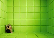 Woman crouching in corner of green padded cell (thumbnail)