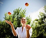 Woman juggling apples in orchard