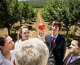 Man showing apple to group in orchard