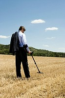 Businessman with metal detector outdoors