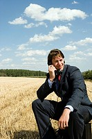 Man on old phone in wheat field
