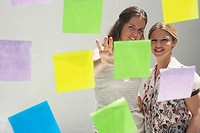 Two young women seen through window with colored swatches / PostIt Notes (thumbnail)