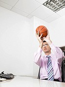 Businessman in an office throwing a basketball