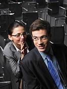 Woman whispering to man sitting in auditorium