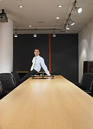 Portrait of young man sitting at boardroom table with miniature table tennis set