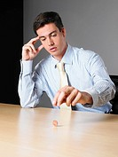 Businessman in an office spinning a penny on a desk