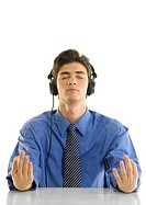 Businessman practicing yoga and listening to music