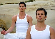 Two young men practicing yoga
