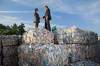 Businessmen shaking hands at a recycling plant