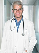 Portrait of mature male doctor in a lobby of a hospital Close up smiling