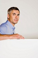 Businessman leaning on cubicle wall