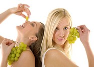 Close-up of two young women holding bunches of grapes