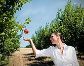 Woman catching apple in orchard