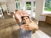 Woman framing face with hands moving into empty house