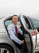 Chauffeur Holding Car Door Open for Smiling Businessman