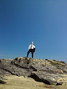Businessman standing on rock