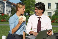Businessman and businesswoman sitting in park working